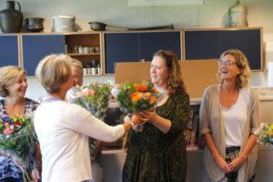 Mevr. Ingrid van Leeuwen ontvangt een bloemetje van mevr. Mangert-Doeksen. Rechts mevr. L. van Benten, de nieuwe voorzitter van de ouderraad.